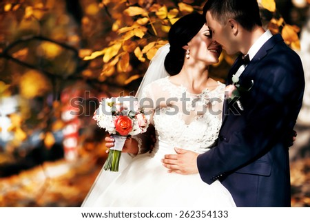 Kissing bride and groom in their wedding day near autumn tree