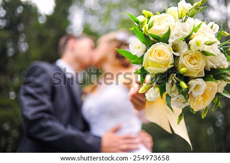 Kissing caucasian couple wedding shot in the park. Focus on bouquet. - stock photo