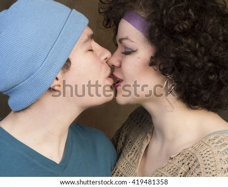 Kissing couple/Attractive young Caucasian couple sharing a kiss against a portrait background - stock photo
