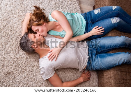 kissing couple couch floor lying down in new home - stock photo
