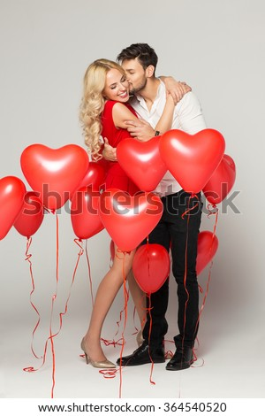 Kissing couple posing on grey background with balloons heart. Valentine's day. - stock photo