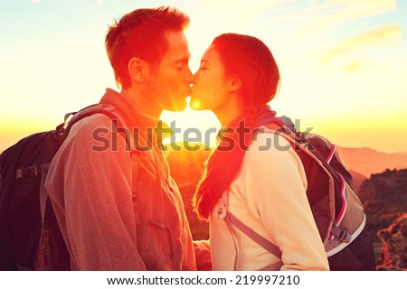 Kissing couple romantic at sunset. Romance kiss in nature. Young woman and man. - stock photo