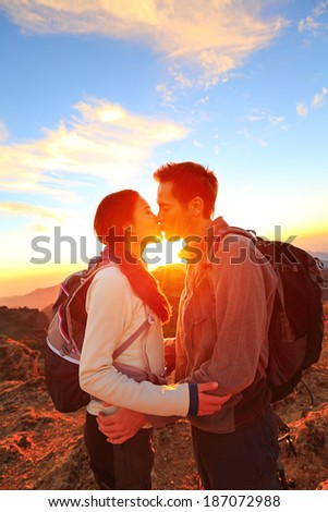 Kissing couple - romantic lovers hiking at sunset sharing kiss enjoying sunshine and love on beautiful hike in mountain nature landscape. Young interracial couple, Asian woman, Caucasian man in love. - stock photo