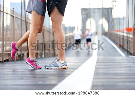 Kissing couple running - Love sport romantic dating concept. Closeup of running shoes and girl standing on toes to kiss boyfriend during jogging workout training on Brooklyn Bridge, New York City, USA - stock photo