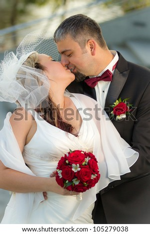 Kissing happy young couple - stock photo