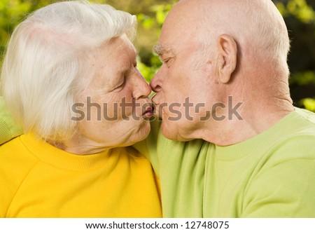 Kissing senior couple - stock photo