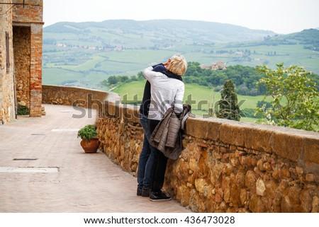 Kissing senior couple in street medieval city Pienza in Tuscany, Italy. - stock photo