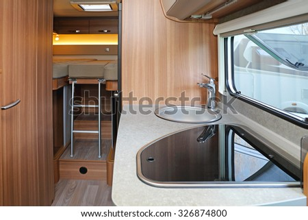 Kitchen and bedroom in camping van - stock photo