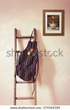 Kitchen apron hanging on the rung of a rustic wooden ladder with spoons and whisk - stock photo