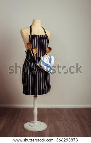 Kitchen apron on vintage mannequin with cooking utensils