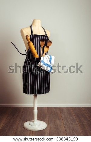 Kitchen apron with baking utensils in the pocket with vintage tone - stock photo