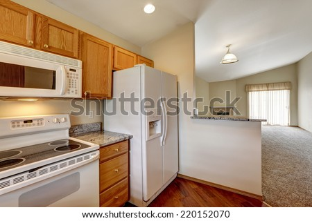 Kitchen area in empty house. White appliances and wooden cabinet.