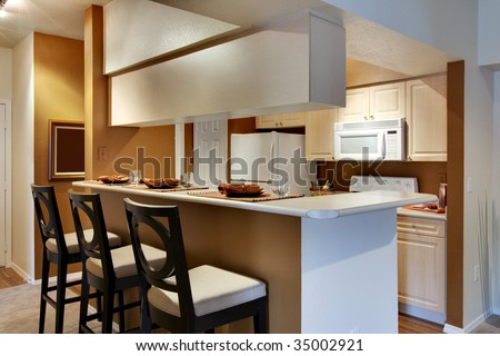 Kitchen area of apartment with high bar-style countertop