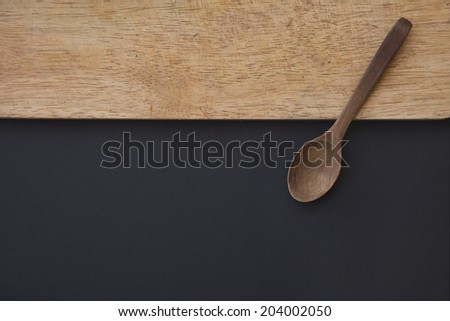 Kitchen background with copy space, Old Wooden cutting board and dark black table surface. Restaurant menu background - stock photo