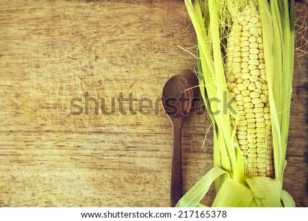Kitchen background with copy space, Old Wooden table surface with corn and wooden spoon. Restaurant menu background, Autumn harvest background - stock photo