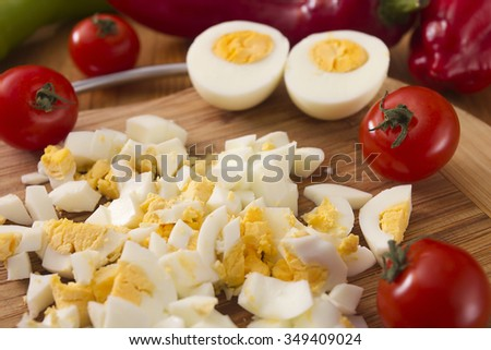 Kitchen board with finely chopped eggs, used as an ingredient in various cookery. - stock photo