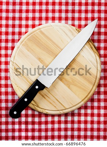 Kitchen chef's knife on wooden chopping board - stock photo