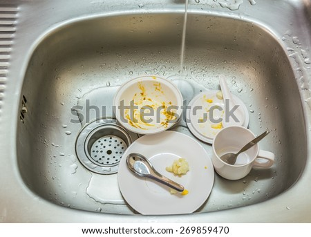Kitchen conceptual image. Dirty sink with many dirty dishes and kitchenware. - stock photo