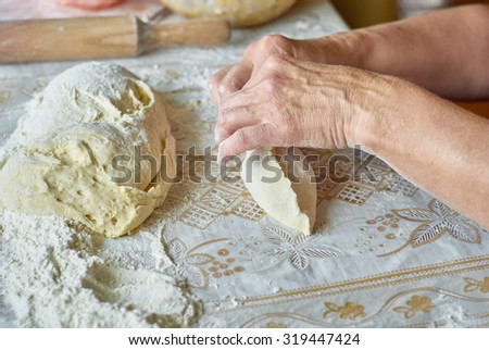Kitchen, cooking pies with dough on the table, close up