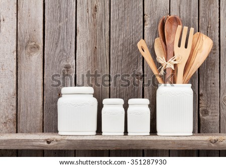 Kitchen cooking utensils on shelf against rustic wooden wall - stock photo