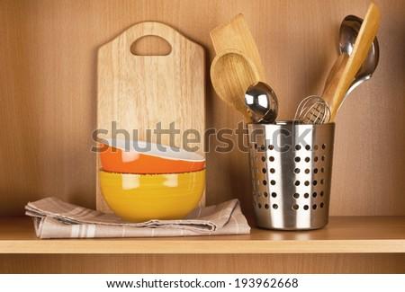 Kitchen cooking utensils  on wooden shelf - stock photo