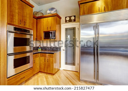 Kitchen corner in luxury house. Steel stainless appliance, large refrigerator and black granite tops