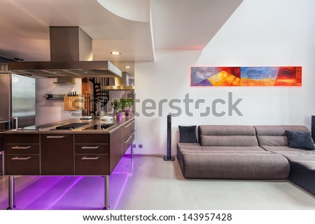 Kitchen counter and sofa in a spacious apartment - stock photo