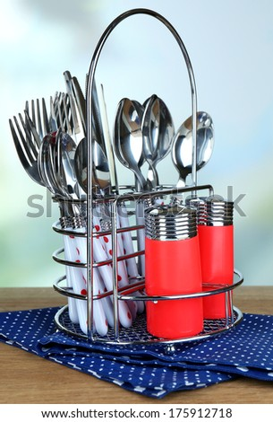 Kitchen cutlery in metal stand on wooden table on bright background - stock photo