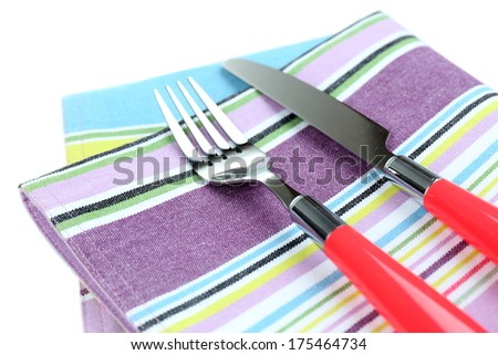 Kitchen cutlery on color napkin close up