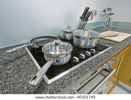 kitchen detail with induction electric hob and cooking pans - stock photo