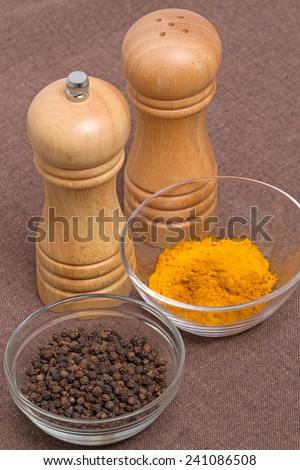 Kitchen equipment - pepper mill and salt shaker. Spices - pepper pots and turmeric - stock photo