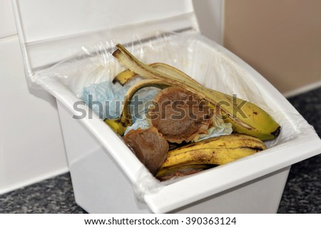 Kitchen food waste in a lidded collecting box with paper, tea bags and banana skins for recycling on a compost heap.