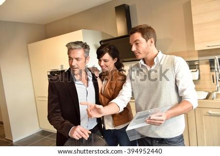 Kitchen furniture salesman giving advice to couple - stock photo
