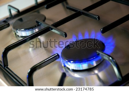 Kitchen gas burner with blue flame. - stock photo