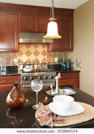 Kitchen granite counter top with plate and glass with stove and kitchen. - stock photo