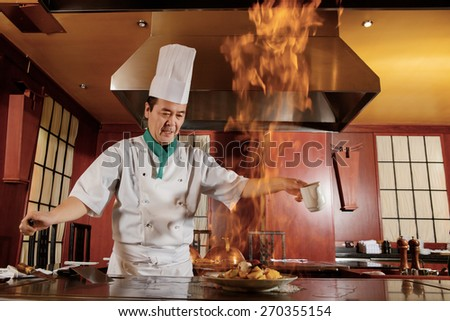 Kitchen hell. Japanese cook frying a vegetarian meal in burning flame of spirit on restaurant kitchen - stock photo