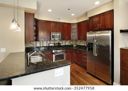Kitchen in condominium with cherry wood cabinetry - stock photo