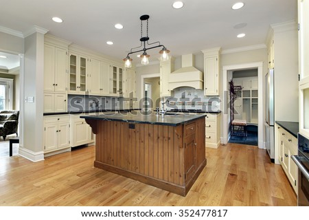 Kitchen in luxury home with black granite and wood center island