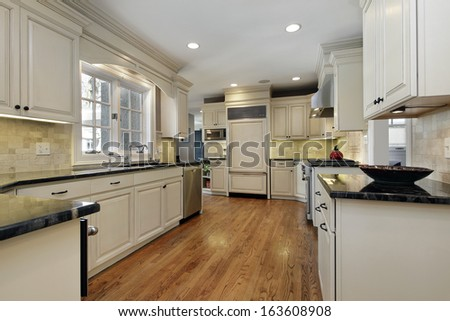 Kitchen in luxury home with black granite counters - stock photo