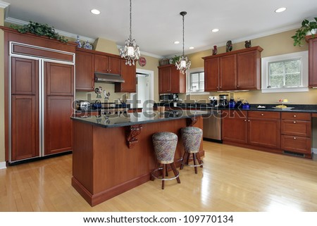 Kitchen in luxury home with cherrywood cabinetry - stock photo