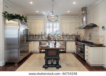 Kitchen in luxury home with cream colored cabinetry - stock photo