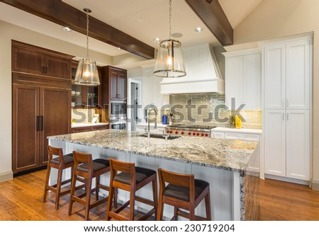 Kitchen in Luxury Home with Island and Cabinetry - stock photo