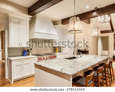 Kitchen in Luxury Home with Island, Sink, Cabinets, and Hardwood Floors - stock photo