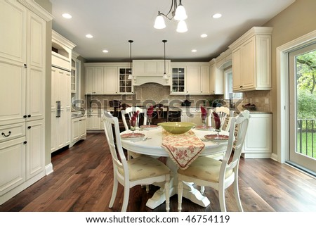 Kitchen in luxury home with light wood cabinetry - stock photo
