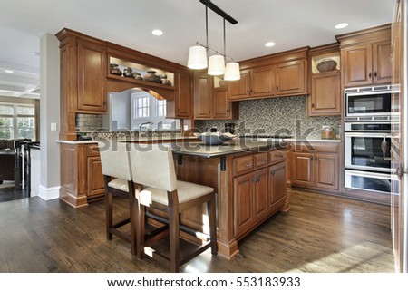 Kitchen in luxury home with oak wood cabinetry and center island.