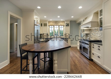 Kitchen in luxury home with wood top island - stock photo