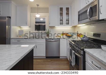 Kitchen in modern home with white Marble counter tops wooden floor and all new appliances.  - stock photo