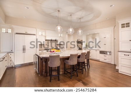 Kitchen in New Luxury Home at Night with Lights on - stock photo