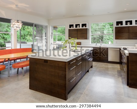 Kitchen in New Luxury Home with Island, Sink, Cabinets, and Table - stock photo