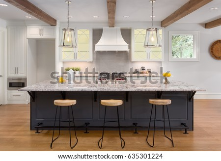 Kitchen in New Luxury Home with Large Island, Hardwood Floors, Range Hood, and Glass Fronted Cabinets, Horizontal Orientation; Lights are on